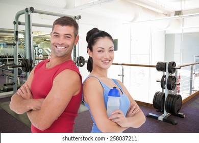 Fit man and woman smiling at camera together against empty weights room with bench press