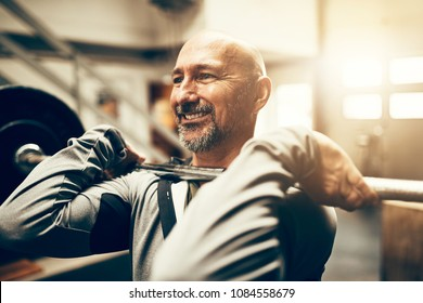 Fit mature man in sportswear smiling while lifting heavy weights during a workout session in a gym
