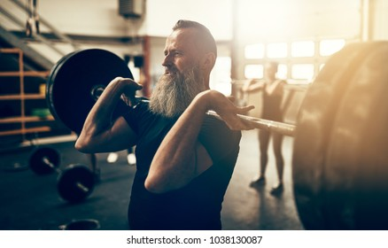 Fit mature man in sportswear standing in a gym lifting heavy weights during a workout session