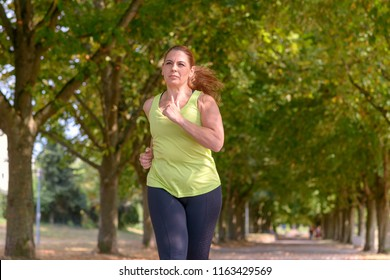 Fit middle-aged woman jogging along a tree-lined avenue through a park approaching the camera in a health and fitness or active lifestyle concept