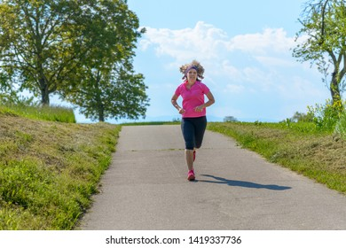 Fit middle-aged woman jogging on a country road through green grassy fields in spring in a concept of a healthy active lifestyle
