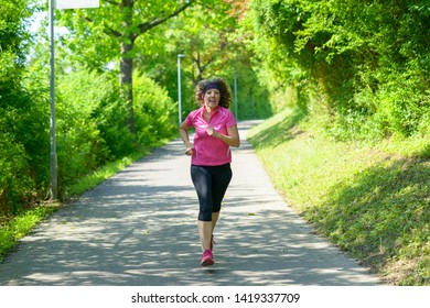 Fit middle-aged woman out jogging in spring approaching the camera along a winding road through leafy green trees conceptual of a healthy active lifestyle