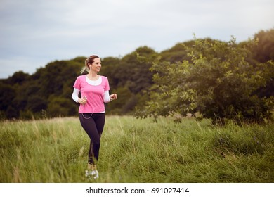 Fit middle-aged woman walking through a rural field listening to music on her mobile phone using earbuds looking to the side with a happy smile in a healthy outdoors lifestyle concept