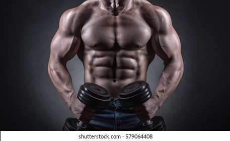 Fit muscular bodybuilder man exercising with dumbbell on dark background