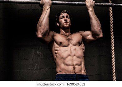 Fit muscular bodybuilder man posing on dark background