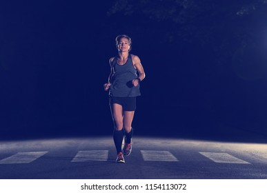 fit muscular female runner training for marathon running at night on beautiful road in nature.
