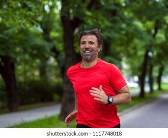 fit muscular male runner training for marathon running on beautiful road in nature.