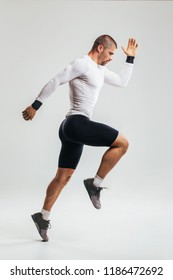 Fit and muscular man jumping/ Studio shoot of fit athlete jumping against white background