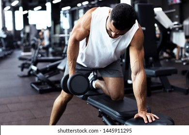 Fit and muscular man trains with dumbbells.