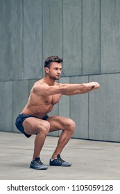 Fit muscular shirtless young man working out in town doing squats in a forecourt of a commercial building in a health and fitness concept