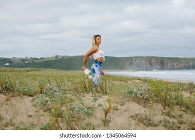 Fit muscular sporty young woman stretching quadriceps and exercising at the beach. Summer morning outdoor fitness workout. Playa de Xago, Asturias, Spain.