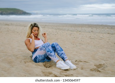 Fit muscular sporty young woman doing sit ups for core training at the beach. Summer morning outdoor fitness workout.