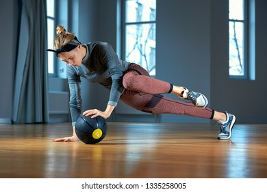 Fit and muscular woman doing intense core workout with kettlebell in gym. Female exercising at crossfit gym.
