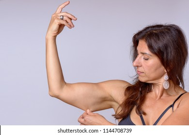 Fit muscular woman pinching the skin of her upper arm with her fingers as she shows of her toned physique in a health and fitness concept