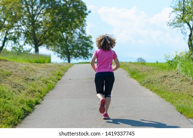 Fit muscular woman running or jogging away from the camera on a rural road through fields in spring conceptual of a healthy active lifestyle