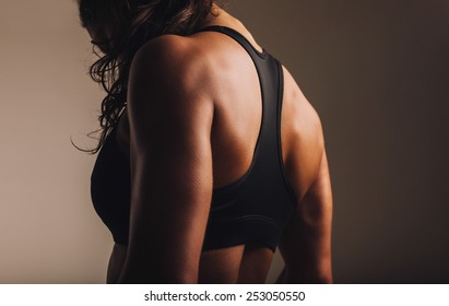 Fit and muscular woman in sports bra standing with her back towards camera. Rear view of fitness female with muscular body.