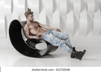 Fit night club dancer in casual clothes with naked torso sitting on chair against modern abstract interior