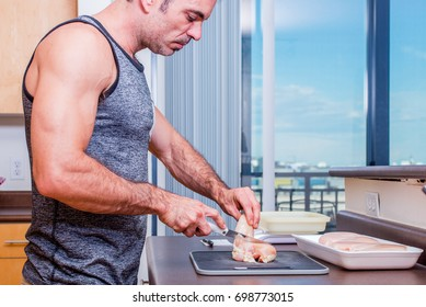 Fit, older male, cutting raw chicken. Healthy meal prep.