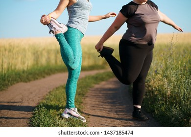 Fit and overweight female friends jogging at outdoor workout. Friendship, motivation, personal trainer, group workout, weight loss, sports and health care