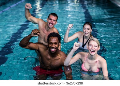 Fit people cycling in the pool with arms raised