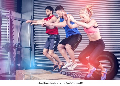 Fit people doing exercises with box at crossfit gym