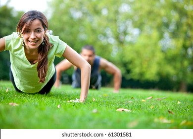 Fit people doing push-ups at the park