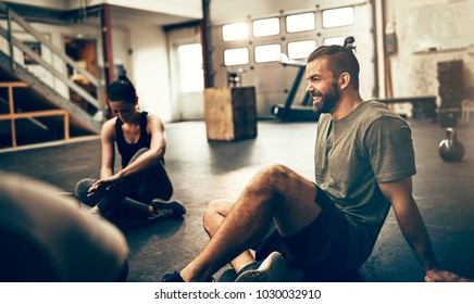 Fit people in exercise gear sitting together on the floor of a gym talking and laughing together after a workout