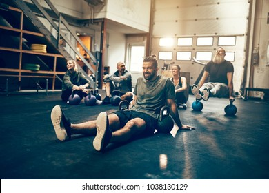 Fit people in exercise gear sitting on the floor of a gym relaxing together after a workout session