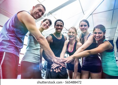 Fit people putting their hands together in gym