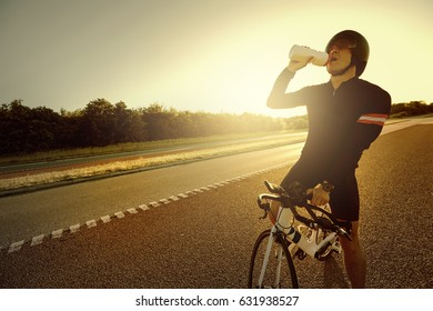 The fit person resting and drinking water from the bottle sitting on a bicycle in the evening.