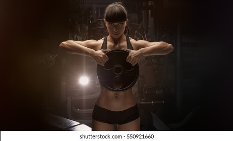 Fit power athletic confident young woman crossfit trainer doing exercises with heavy weight barbell plate in gym rising hand. Fitness muscular body, strong hand on dark background Pumping up muscles
