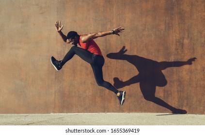 Fit mächtigen jungen Mann, der einen Running-Jump macht, der Schatten auf eine Wand wirft. Starker schwarzer Läufer Training auf heißen Sommer.
