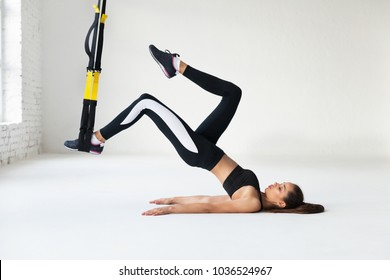 Fit pretty young woman doing fly yoga stretching exercises with trx fitness straps  in fitness training white gym loft classroom. Sport healthy lifestyle concept. Copy space.