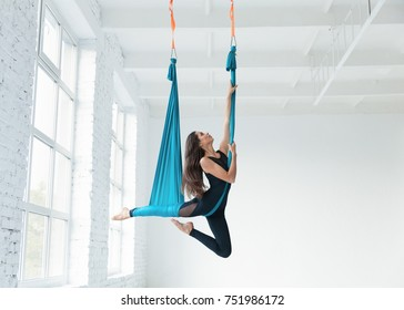 Fit pretty young woman doing fly yoga stretching exercises  in fitness training white gym loft classroom. Sport and healthy lifestyle concept. Copy space, empty space for text.