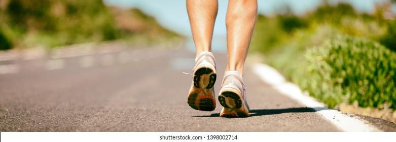 Fit run runner man jogging feet closeup running shoes banner panorama. Athletes legs walking on street for summer marathon.
