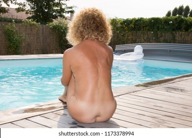 fit senior woman nude on the beach pool side at home nudism liberty concept