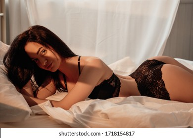 Fit and sexy woman with dark brown hair laying among bed sheets wearing black lace lingerie and looking seductive showing her hips while slightly smirking