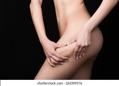 Fit sexy woman holding showing cellulite area.Woman pinches her thigh to control cellulite.Plastic surgery,healthy nutrition,fat lose,liposuction,healthy lifestyle sport and cellulite removal concept