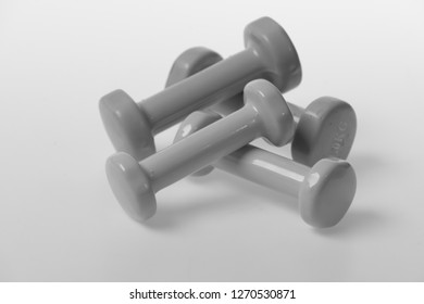 Fit shape and sport concept. Pairs of dumbbells made of blue and pink plastic on white background. Barbells in small size making pattern, close up. Health regime and fitness symbols