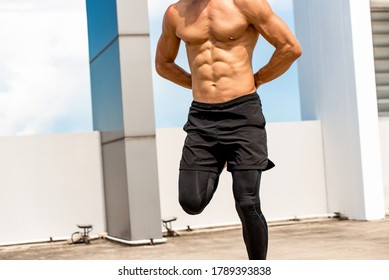 Fit shirtless athletic man doing kick butt exercising outdoors on rooftop, home workout concept