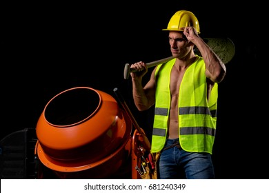fit shirtless worker with tools and concrete mixer