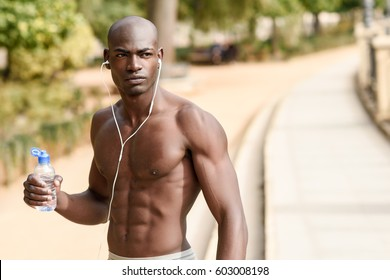 Fit shirtless young black man drinking water after running in urban background. Young male exercising with naked torso listening to music with headphones.
