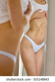 """Fit and slim"" and loose weight concept - mirror reflections of the young woman curves"