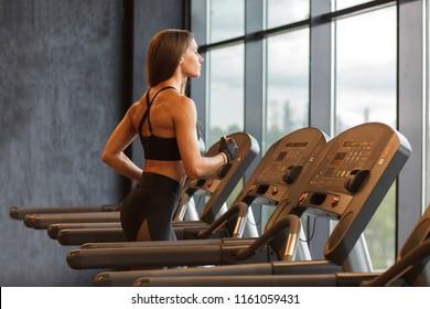 fit slim woman running on treadmill in gym