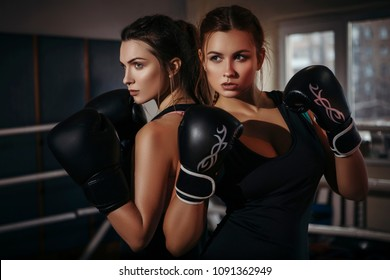 Fit slim young beautiful brunette women boxing in sportswear. Dark dim light. Toned image
