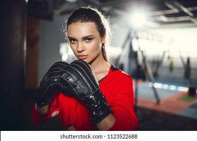 Fit slim young beautiful brunette woman boxing in sportswear. Dark dim light. Toned image