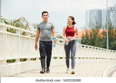 Fit smiling Asian man and woman walking on bridge with water bottles after morning run