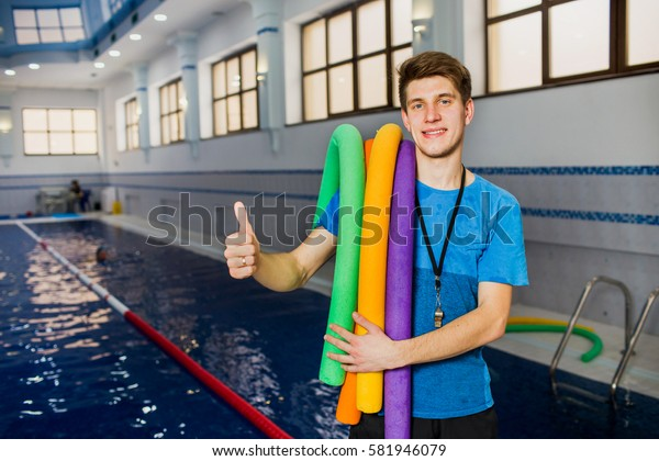 Fit smiling man holding foam roller and showing thumbs up looking at camera at swimming pool. Young swimming instructor