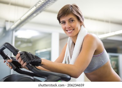 Fit smiling woman working out on the exercise bike at the gym
