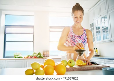 Fit smiling young woman preparing healthy fruit juice from an assortment of fresh fruit using a manual juicer in her kitchen , copy space on a high key window background